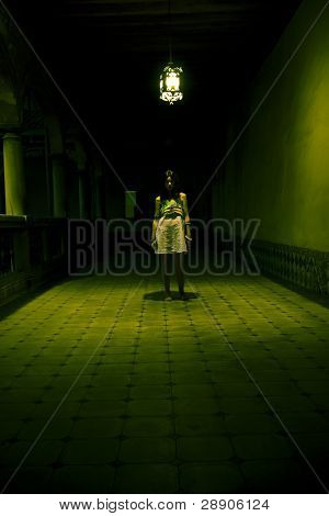 Young woman lost in spooky dirty corridor.