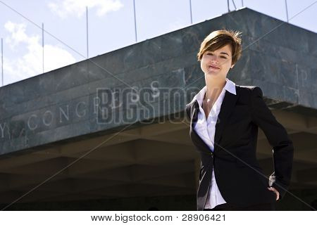 Smiling businesswoman against urban background.
