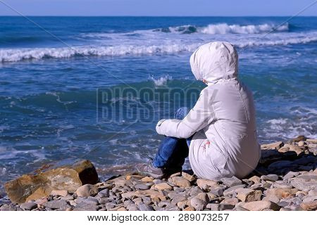 Woman In A White Down Jacket And Hood Sits On The Shore And Looks At The Stormy Sea Waves Beating Ag