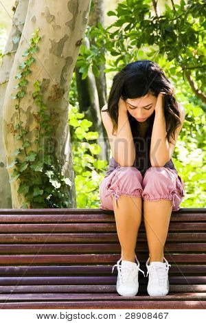 Young sad woman sitting on a park bench.