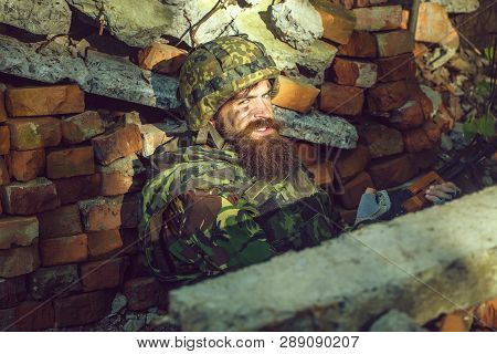 Man Soldier With Dust Grime Beard And Angry On His Face In Helmet And War Camouflage And Rifle In Hi