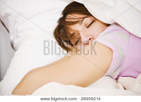 Young beautiful woman sleeping in white sheet.