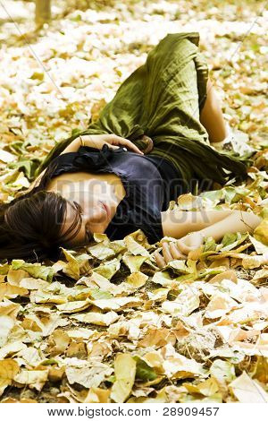 Young woman laying over golden leaves.