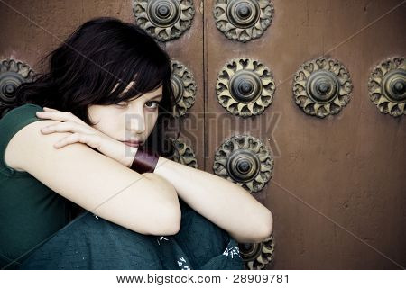 Thoughtful beautiful woman over antique background.