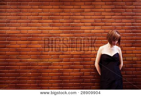 Sad woman portrait posing over red brickwall