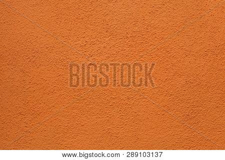 Orange painted stucco wall on Burano Island in the Venetian Lagoon near Venice, Italy. Background texture.