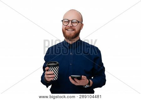 Handsome Happy Smilng Bearded Man In Glasses And Dark Blue Shirt, Holding Mobile And Cup Of Coffee