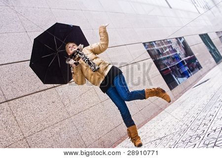 Happy young blond woman in a rainy day.