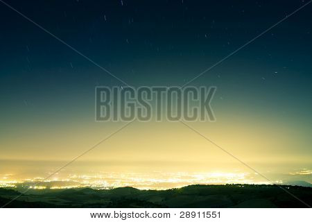 Stars raining over city at night. Long exposed picture.