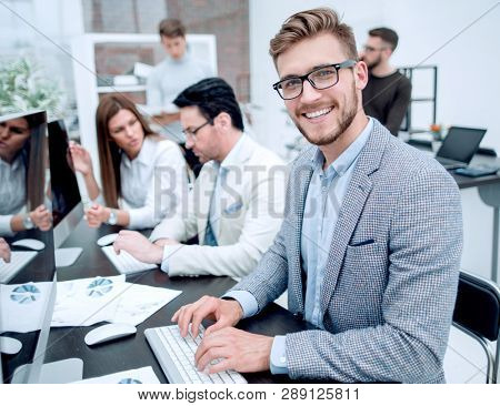 smiling businessman uses a computer to analyze financial data