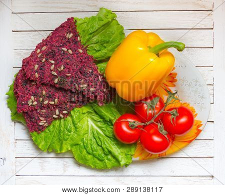 Beetroot Vegan Dry Bread Loaves, Pepper, Tomatoes And Green Lettuce On Plate On White Wooden Table