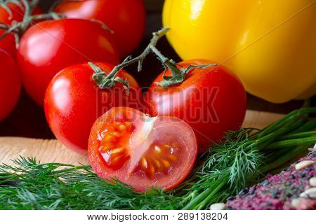 Ripe Red Slice Of Tomato With Dill And Yellow Pepper On Kitchen Board