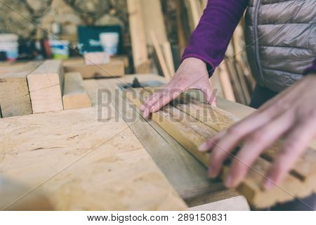 A woman works in a carpentry workshop. The girl handles the wood. Woman in the male profession. Feminism. The girl learns to work with carpentry tools. Female hands closeup. A circular saw. poster