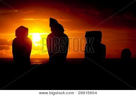 Four moai against dramatic red and orange sunset in Easter Island poster