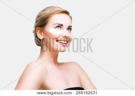 Image of smiling blonde women with gel pads under eyes.
