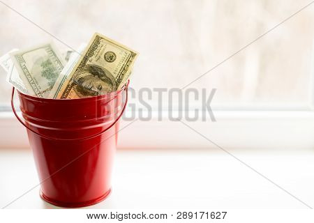 Dollar Bills In Red Pail. On White Window.light Background. Place For Text. Top View. A Lot Of Money