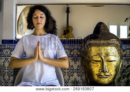 Portrait Of Young Woman In White Tshirt And With Short Hair Sitting In Meditation Pose In The Flat N