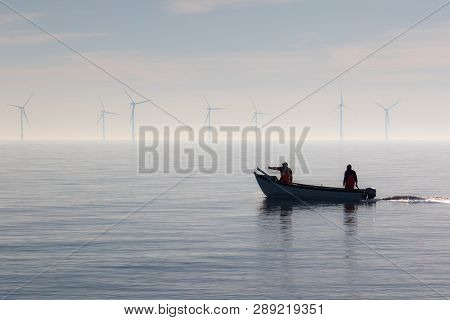Sustainable Resources Alternative Lifestyle. Small Fishing Boat With Offshore Wind Turbines. Calm Mi