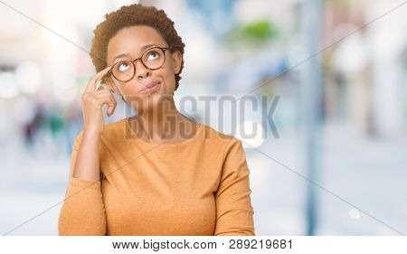 Young beautiful african american woman wearing glasses over isolated background with hand on chin thinking about question, pensive expression. Smiling with thoughtful face. Doubt concept.