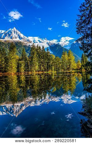Concept of active and ecotourism. Fantastic sunset in the autumnal Alps. Stunning reflections of snowy peaks in the lake water. Mountain resort of Chamonix, the foot of Mont Blanc poster