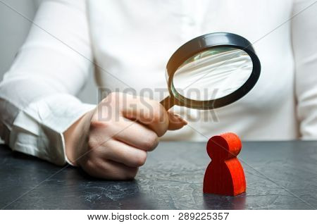 Business Woman Examines A Red Man's Figure Through A Magnifying Glass. Analysis Of The Personal Qual