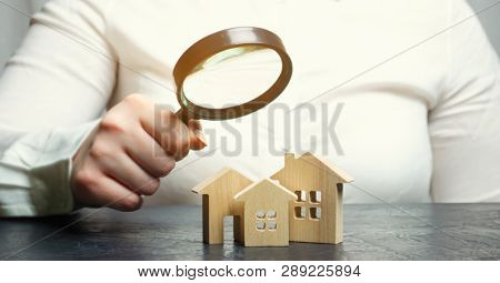 A woman is holding a magnifying glass over a wooden houses. Real estate appraiser. Property valuation / appraisal. Find a house. Search for housing. Real estate market analysis. Selective focus poster