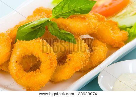 Calamari with crispy floured or onion ring with crispy flour - deep fried.