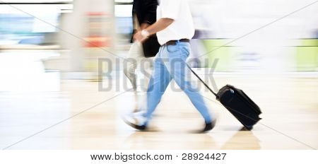 Two business men moving quickly on the terminal. Panning technique.