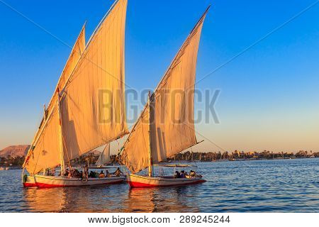 Felucca Boats Sailing On The Nile River In Luxor, Egypt. Traditional Egyptian Sailing Boats