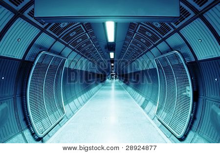 Cylindrical tunnel for pedestrians, blue toned.