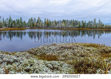 Autumn And Winter Landscape. Two Beautiful Seasons Collide And Are Reflected In A Wilderness Lake Wi
