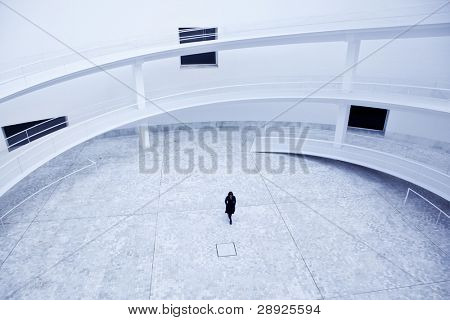 Woman in black walking over an abstract lobby