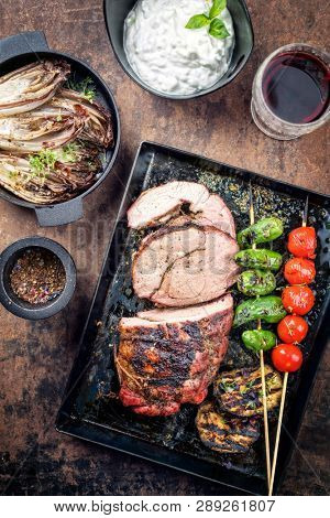 Barbecue marinated lamb roast with vegetable, chicory and tzatziki as top view on a metal sheet