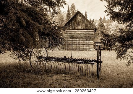 Pioneer Homestead. Antique Rusted Plow And Exterior Wall Of A Traditional Log Cabin In The American