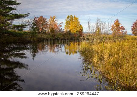 Autumn Reflections Landscape. Vibrant Fall Foliage Reflected In A River Flowing Through The Hiawatha