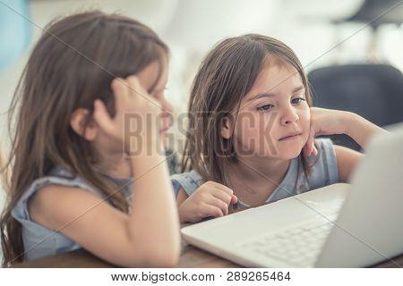 Cute Twins Little Sisters Usin Modern Laptop.