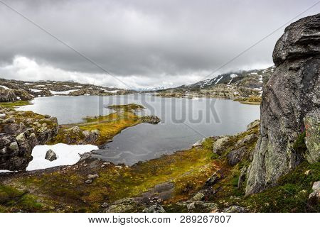 Amazing norwegian landscape with clear lake and snowy mountains
