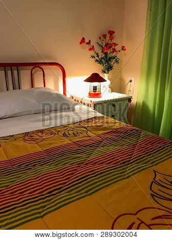 Vibrant Colored Interior Of A Bedroom. Pillow And Colorful Coverlet On The Bed. Bedroom Interior Des