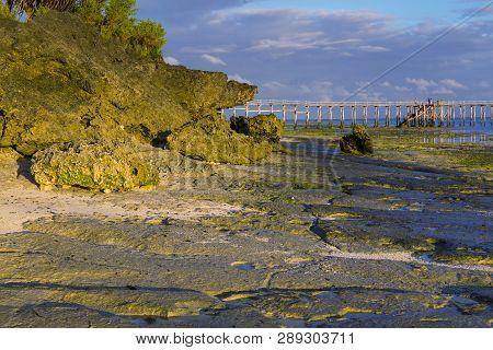 Morning On The Ocean Coast At Low Tide. Coastal Rocks, Wooden Pedestrian Bridge Leading Into The Wat