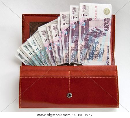 orange leather wallet full of one hundred roubles on light background