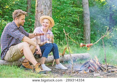 Hand gesture game decide who win. Couple tourists throwing their gesture while sit log near bonfire. Man and girl play hand gesture game. Couple play rock paper scissors hand game. Winner eats first poster