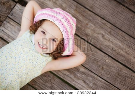 Pretty child lying on wooden surface.