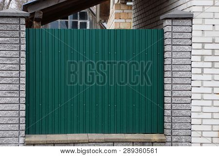 Part Of The Fence Of Green Metal And Gray Brick In The Street