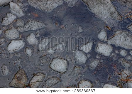 Natural Texture Of Gray Water And A Piece Of White Ice In A Puddle