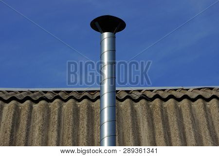 Long Metal Pipe On A Gray Slate Roof Against A Blue Sky