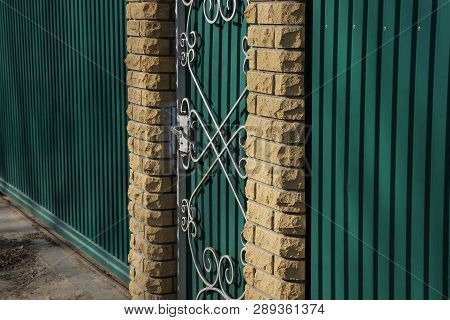 Part Of The Fence With A Closed Door Of Green Metal And Brown Brick