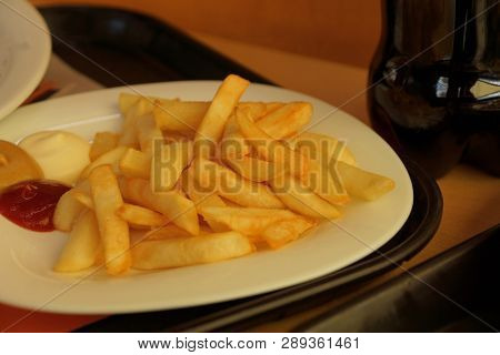 Fried Potatoes On A White Plate With Sauces On A Brown Table