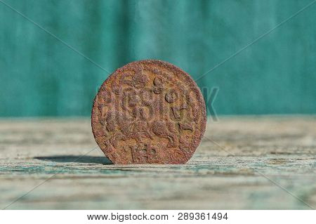 Old Brown Copper Coin Stands On A Gray Table