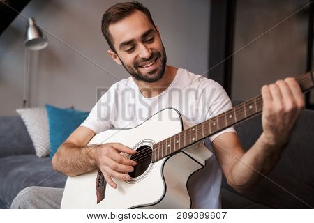 Photo of attractive man 30s wearing casual t-shirt playing acoustic guitar while sitting on sofa in apartment poster