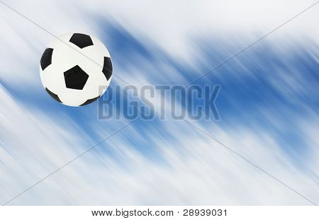 a Soccer ball kicked high into the air showing motion